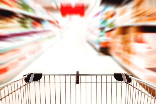Kundvagn mellan suddiga butikshyllor